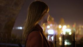 Young beautiful woman walking at night in the city. Red-haired woman on the stree. Slow Motion stock footage