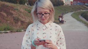 Young beautiful woman walking in the park near the lake using her smartphone, texting her friends, browsing internet stock video