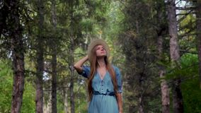Young beautiful woman walking through a pathway in a pine forest stock video