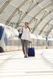Young beautiful woman walking with suitcase at train station Stock Photo