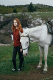 Young beautiful woman is walking with a white horse in the mountains, nature, beauty Royalty Free Stock Image