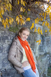 Young beautiful woman in warm clothes posing against stone wall Stock Photo