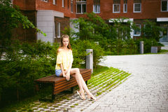 Young beautiful woman, warm summer sunny day. Portrait of a young pretty woman in blue denim jeans shorts sitting on a bench in courtyard of a residential royalty free stock photos