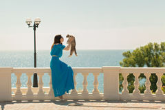 Young beautiful woman on the waterfront in azure long dress is p Royalty Free Stock Photography