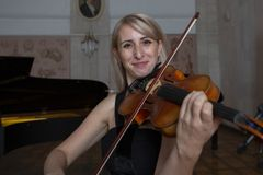 Young beautiful woman with wavy blonde hair playing viola, holding bow hovering over instrument on her shoulder and smiling, looki royalty free stock images