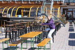 Young beautiful woman wear sitting in outdoor restaurant. Skiing resort in Alps. Royalty Free Stock Photography