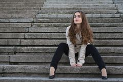 Young beautiful woman wearing beige jacket sitting on concrete stairs Royalty Free Stock Photos
