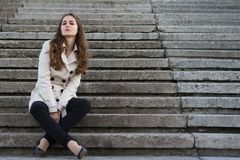 Young beautiful woman wearing beige jacket sitting on concrete stairs Stock Photos
