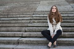 Young beautiful woman wearing beige jacket sitting on concrete staircase. Young beautiful woman wearing beige jacket sitting on concrete stairs. Looking to Stock Photos