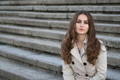 Young beautiful woman wearing beige jacket sitting on concrete stairs. Looking to camera Stock Image