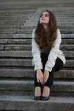 Young beautiful woman wearing jacket sitting on concrete stairs looking up Stock Images