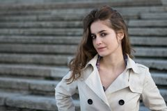 Young beautiful woman wearing beige jacket standing on concrete stairs Stock Images