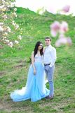 Young beautiful woman wearing blue dress and walking near magnolia with boyfriend. Young beautiful women wearing blue dress and walking near magnolia with stock photography