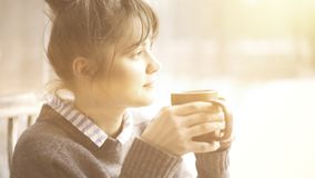 Young beautiful woman wearing a gray sweater is enjoying her tea in a cafe and daydreaming. Toned image. Young beautiful woman wearing a gray sweater is Royalty Free Stock Image