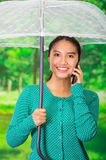 Young beautiful woman wearing a green sweater with umbrella at beautiful autum park, using her mobile phone Stock Images