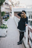 Young beautiful woman wearing hat and coat standing on the embankment Stock Photo