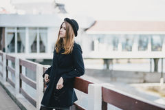 Young beautiful woman wearing hat and coat standing on the embankment Royalty Free Stock Photography
