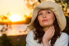 Young and beautiful woman wearing a hat i. N sunset light Stock Image