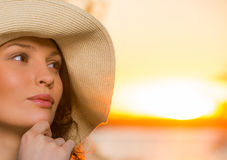 Young and beautiful woman wearing a hat in sunset closeup Stock Photos