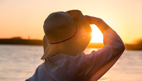 Young and beautiful woman wearing a hat in sunset light looking. Far away. Photo from behind Stock Image