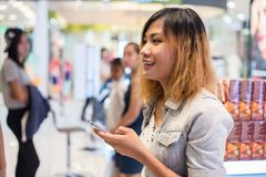 young beautiful woman wearing jean jacket texting on the smartphone walking in the shopping mall. royalty free stock photo