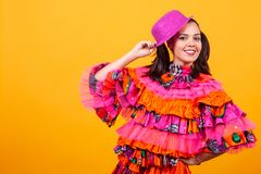 Young beautiful woman wearing a mascarade latino costume. Over yellow background in studio royalty free stock photos