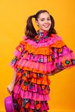 Young beautiful woman wearing a mascarade latino costume. Over yellow background in studio royalty free stock images