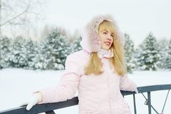 Young beautiful woman wearing pink jacket with a hood admiring winter nature Stock Photos