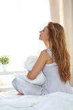 Young beautiful woman wearing pyjamas sitting on her bed holding Stock Image