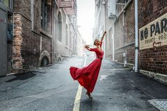Dance is her passion. Mixed media. Young beautiful woman wearing red dress dancing on street. Mixed media Stock Images