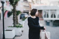 Young beautiful woman wearing total black clothes standing on the city embankment Royalty Free Stock Photography
