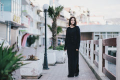 Young beautiful woman wearing total black clothes standing on the city embankment Royalty Free Stock Photo