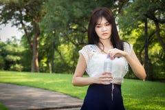 Young beautiful  woman wearing white shirts drinking water at su Stock Photo