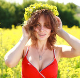 Young beautiful woman wearing a wreath of yellow flowers Royalty Free Stock Photo