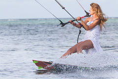 Young beautiful woman in wedding dress kitesurfing Stock Photos