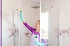 Young beautiful woman in white apron cleaning shower cabin. Cleaning service. Maid cleaning at home stock photography