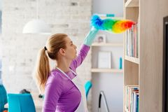 Young beautiful woman in white apron dusting books. Cleaning service. Maid cleaning at home royalty free stock image