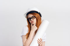 Young beautiful woman on a white  background in a helmet holds a couple, construction, engineer Stock Image