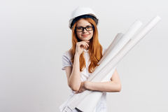 Young beautiful woman on white  background holds blueprints, engineer, construction, smile, hard hat Stock Photography