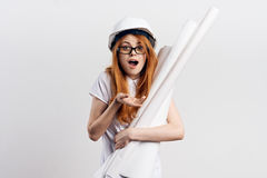 Young beautiful woman on white  background holds blueprints, hard hat, emotions, engineer, construction Stock Photos