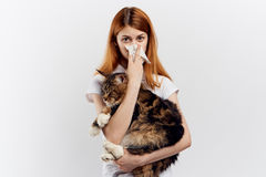 Young beautiful woman on white  background holds a cat, an allergy to pets Royalty Free Stock Photography