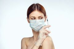 Young beautiful woman on white  background in medical mask holds syringe, portrait, medicine, plastic Stock Photography