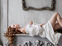 Young beautiful woman in a white baroque dress lying on the mantelpiece. Sexy young beautiful woman in a white baroque dress lying on the mantelpiece Stock Image
