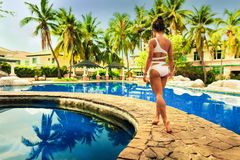 Young beautiful woman in white bikini enjoying summer vacation on the tropical island Bali and relax at swimming pool Royalty Free Stock Photography