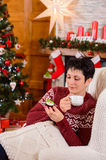 Young beautiful woman in a white chair near the Christmas tree on Christmas night Stock Photos