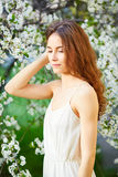 Young beautiful woman in white dress enjoying of blooming tree Royalty Free Stock Photos