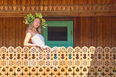 Young beautiful woman in white dress and flower wreath stay in decorative balcony of countryside house at hot and sunny summer day stock images