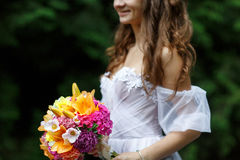Young beautiful woman in a white dress posing with a bouquet Stock Photography