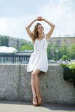 Young beautiful woman in white dress posing outdoors in sunny we Stock Photo