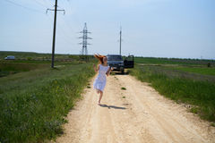 Young beautiful woman in white dress runs across the field royalty free stock photos